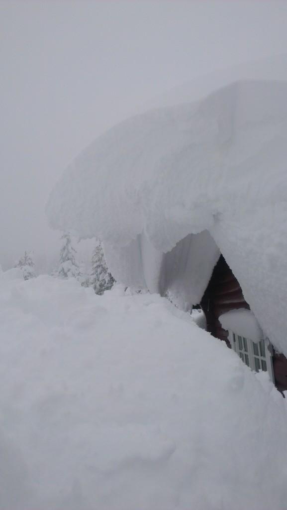 snø henger ut fra taket.